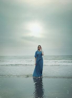 Mark Owen WOMAN IN BLUE DRESS PADDLING IN SEA Women