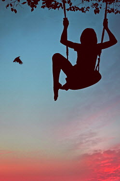 Nicola Smith SILHOUETTE OF GIRL ON SWING AT SUNSET Children