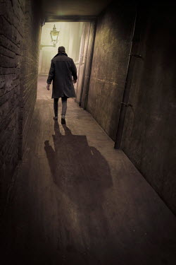 James Wragg SILHOUETTE OF MAN WALKING IN BRICK ALLEYWAY Men