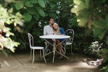 Anna Rakhvalova YOUNG COUPLE BY TABLE CUDDLING IN GARDEN Couples