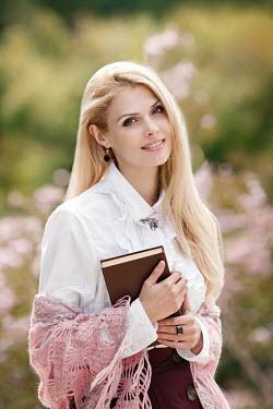 Elena Alferova HAPPY BLONDE WOMAN HOLDING BOOK IN SUMMERY GARDEN Women