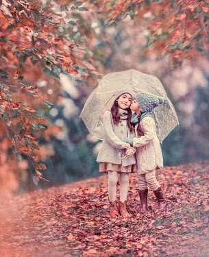 Lilia Alvarado TWO LITTLE GIRLS KISSING IN AUTUMN COUNTRYSIDE WITH UMBRELLA Children