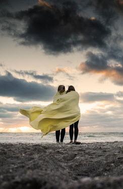 Terry Bidgood TWO GIRLS HUDDLED UNDER BLANKET ON BEACH AT SUNSET Women
