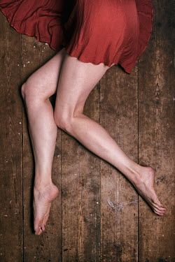 Clayton Bastiani BAREFOOT WOMAN IN DRESS LYING ON FLOORBOARDS Women