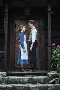 Magdalena Russocka RETRO COUPLE STANDING OUTSIDE WOODEN HOUSE Couples