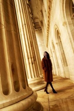 Gary Isaacs WOMAN WALKING BY PILLARS OF GRAND BUILDING Women