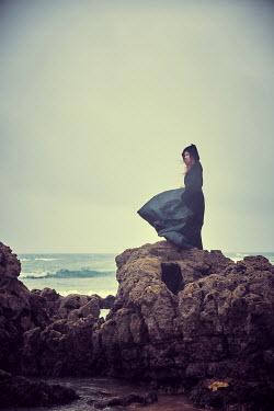 Chris Reeve WOMAN STANDING ON ROCKS BY SEA Women