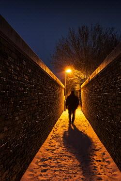 Tony Watson MAN WALKING DOWN SNOWY ALLEYWAY AT NIGHT Men