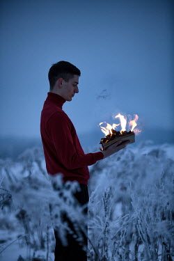 Magdalena Russocka YOUNG MAN BURNING BOOK IN FIELD Men