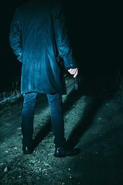 Magdalena Russocka MAN HOLDING HANDGUN ON ROAD AT NIGHT Men