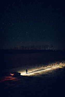 Magdalena Russocka MAN STANDING IN FRONT OF CAR HEADLIGHTS Men