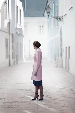 Ildiko Neer Retro woman in pink coat in cobbled town Women