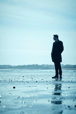 CollaborationJS MAN IN COAT STANDING ON BEACH Men