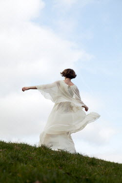 Miguel Sobreira Retro Woman in Floaty Dress On Grassy Hill Women