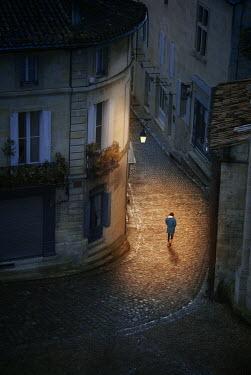 Michael Trevillion WOMAN WALKING IN OLD TOWN AT NIGHT Women