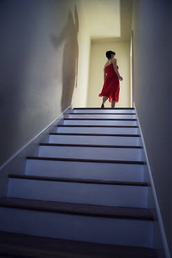 Susan Fox WOMAN IN RED DRESS AT TOP OF STAIRS Women