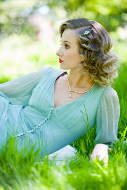 Lee Avison beautiful 1930s woman relaxing in the grass in summer Women
