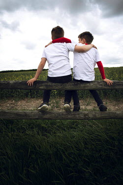 Laura Ranftler TWO YOUNG BOYS SITTING ON A FENCE Children