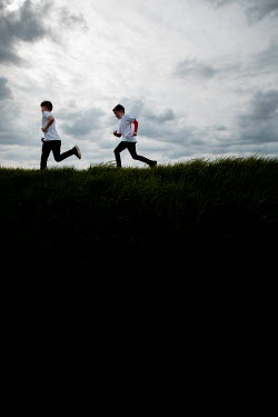 Laura Ranftler TWO YOUNG BOYS RUNNING ON A HILL Children