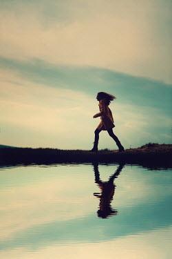 Magdalena Russocka woman walking by river at dusk Women