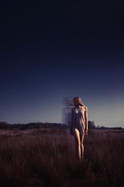 Eva Van Oosten YOUNG WOMAN STANDING IN FIELD AT NIGHT Women