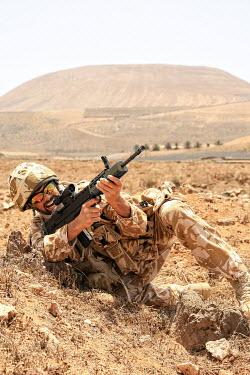 Nik Keevil CAMOUFLAGED SOLDIER WITH GUN IN DESERT Men