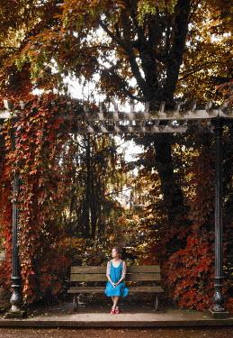 Kyle Stubbs WOMAN SITTING ON BENCH UNDER ARBOR Women