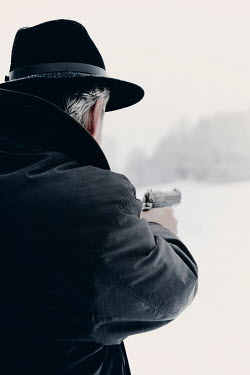 Ilona Wellmann MAN POINTING GUN IN SNOWY COUNTRYSIDE Men