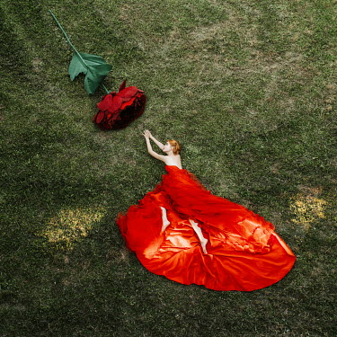 Jovana Rikalo WOMAN IN GOWN LYING WITH HUGE ROSE Women