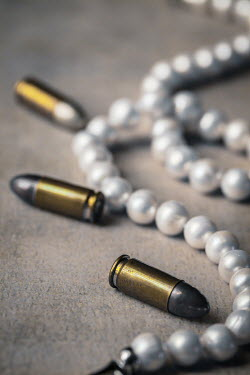 Des Panteva CLOSE UP OF BULLETS WITH PEARL NECKLACE Weapons
