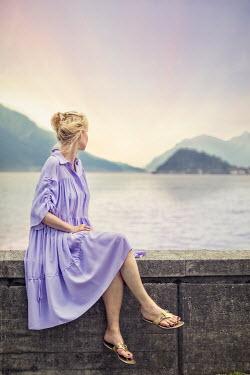 Evelina Kremsdorf WOMAN SITTING BY LAKE AT SUNSET Women