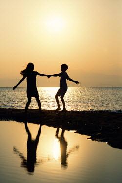 Krasimira Petrova Shishkova SILHOUETTED BOY AND GIRL ON BEACH PLAYING Children