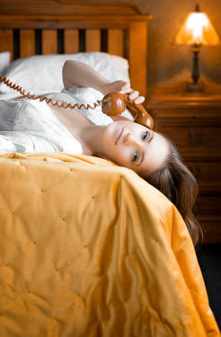 Mary Wethey YOUNG WOMAN LYING ON BED USING TELEPHONE Women