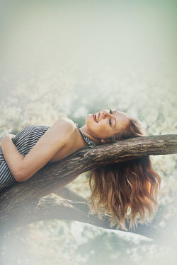 Buffy Cooper YOUNG WOMAN LYING ON TREE BRANCH Women
