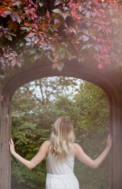 Holly Leedham BLONDE WOMAN STANDING IN GARDEN DOORWAY Women