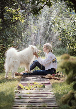 Marta Syrko BLONDE WOMAN STROKING WHITE DOG Women