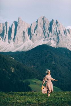 Marta Syrko WOMAN WALKING IN ALPINE MEADOW Women