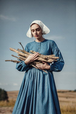 Magdalena Russocka historical woman holding bunch of firewood in field Women