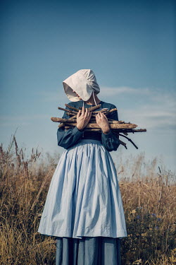 Magdalena Russocka historical woman carrying bunch of firewood in field Women