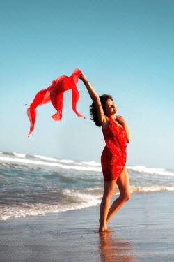 ILINA SIMEONOVA WOMAN HOLDING SCARF ON WINDY BEACH Women