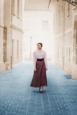 Ildiko Neer historical woman walking in cobbled town Women