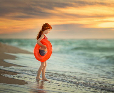 Lilia Alvarado LITTLE GIRL WITH RUBBER RING ON BEACH Children