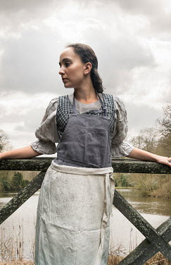 Stephen Mulcahey A woman, wearing a maids costume standing on a wooden  bridge Women