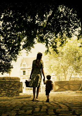 Stephen Mulcahey A silhouette of a mother and son walking towards the station Children