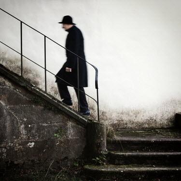 Manuela Deigert OLD MAN WALKING UP OLD STEPS Men