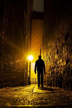 Stephen Mulcahey A silhouette of a man walking down a narrow alleyway Men