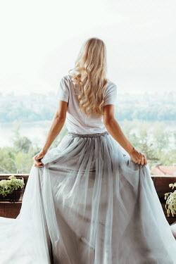 Tijana Moraca BLONDE WOMAN IN WHITE DRESS ON BALCONY Women