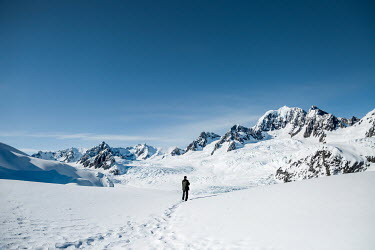 Evelina Kremsdorf MAN IN SNOWY LANDSCAPE WITH MOUNTAINS Men