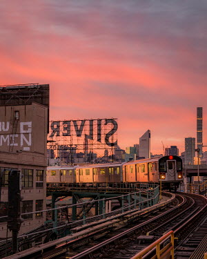Paul Sheen TRAIN IN CITY AT SUNSET Railways/Trains