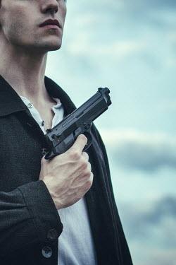 Magdalena Russocka close up of modern man holding gun Men